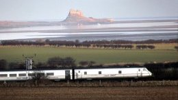 A train regarding the East Coast Line, passes Holy Island
